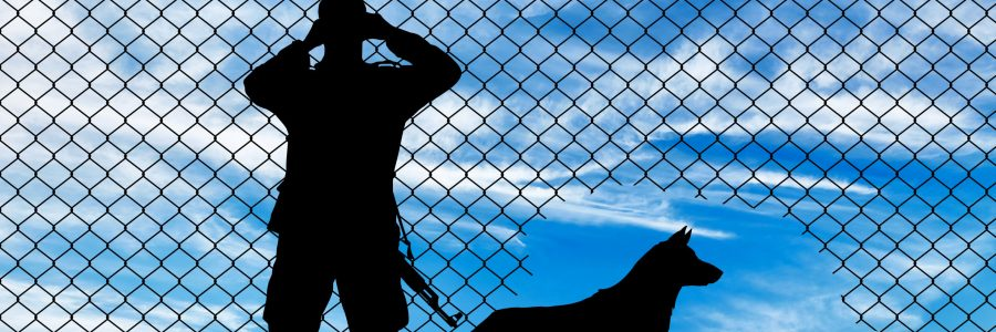 49176745 - concept of the refugees. silhouette of a border guard and a dog near the hole in the fence